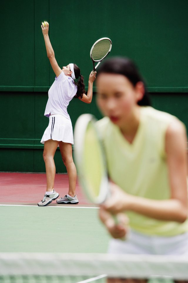 Women's doubles team serving