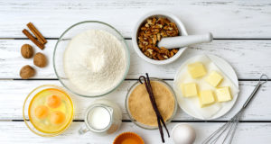 Baking cake in rural kitchen - recipe ingredients (eggs, flour, milk, butter, sugar, walnuts, spices) on white wooden table from above.