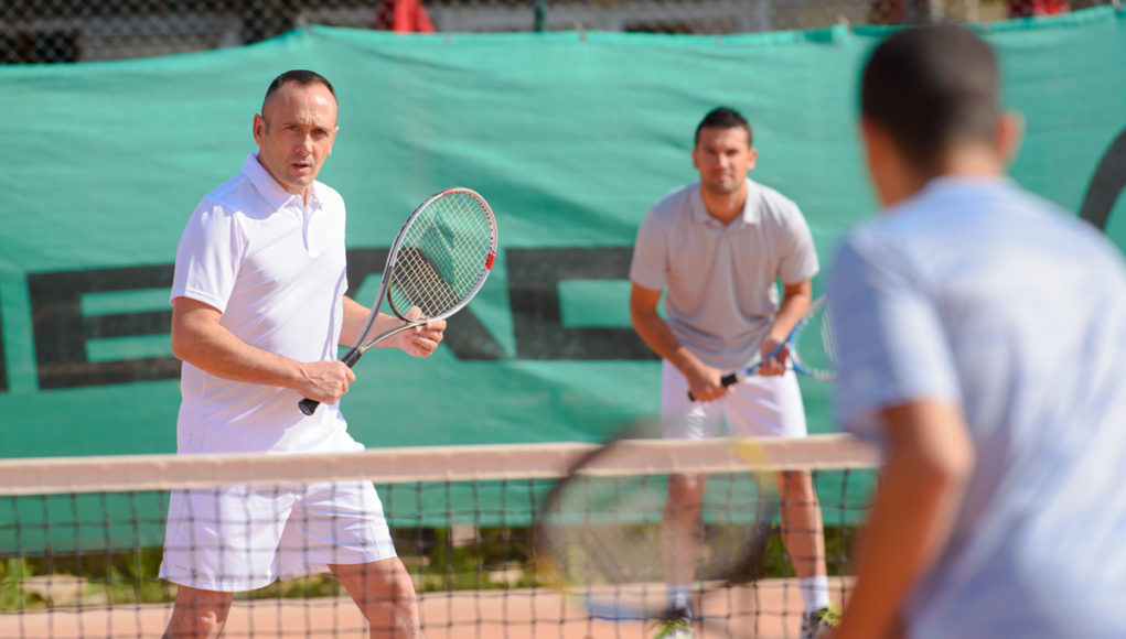 Men playing tennis doubles