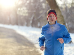 Man out in winter weather for his daily run jogging on a paved road in a snowy landscape in a fitness and healthy lifestyle concept, close up upper body