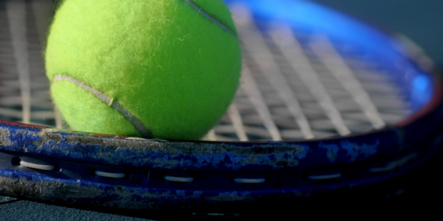 tennis ball resting on a tennis racquet