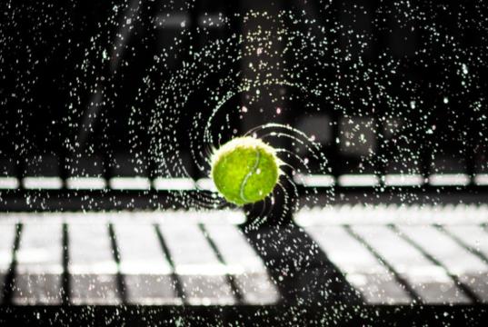 wet tennis ball flying through the air
