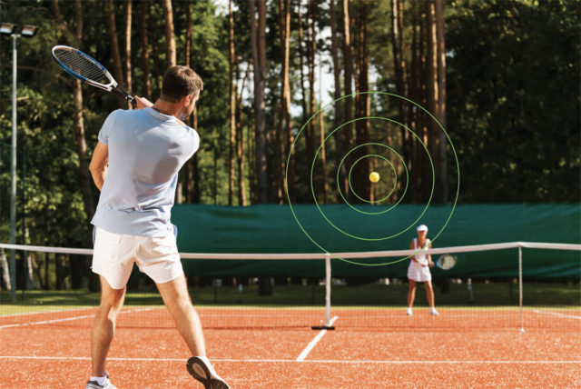 Man and woman playing tennis on a red clay court.