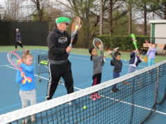 Fieldstone instructor teaching tennis skills to young students