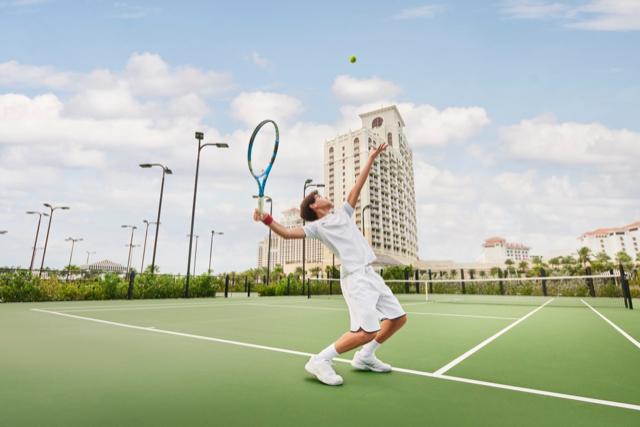 Young boy playing tennis at Baha Mar.