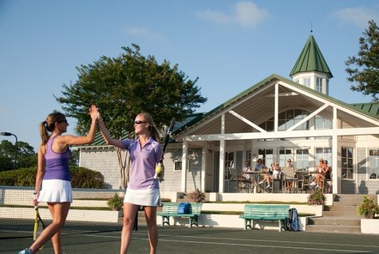 Two women playing tennis on a clay court in Sandestin, FL.