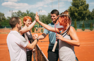Four young friends giving a high-five after tennis training. Selective focus.