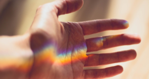 palm side of man's hand with a rainbow of light