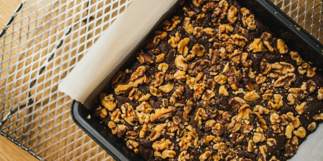 brownies in a pan covered in nuts