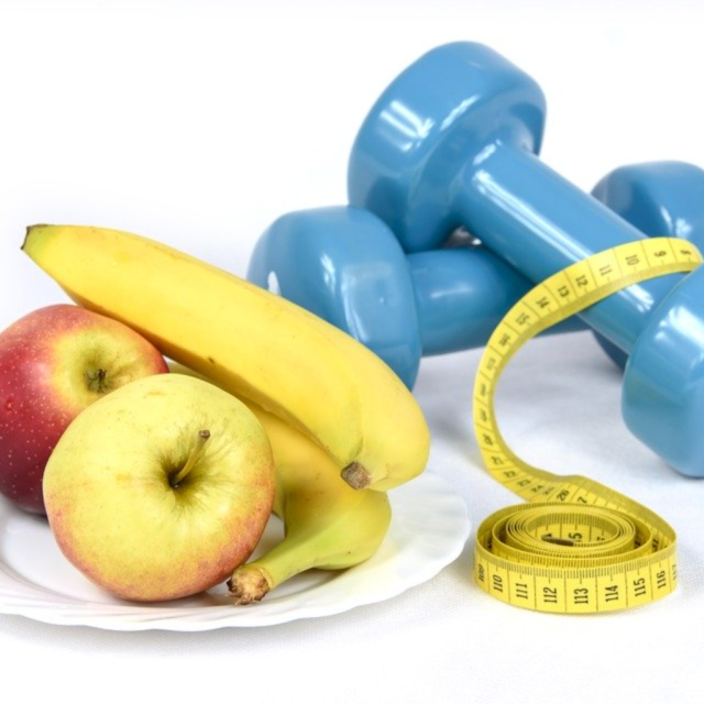 A plate of fruit next to a pair of dumbbells and a measuring tape.