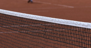 Close up of a tennis net on a red clay court