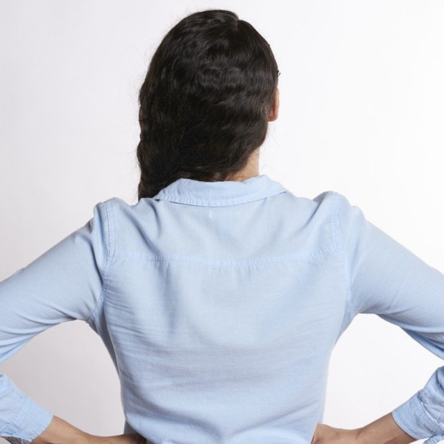 Photo of woman taken from behind while she holds her hands at her side as if she is experiencing back pain.
