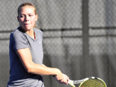 Female tennis player in the middle of a backhand swing