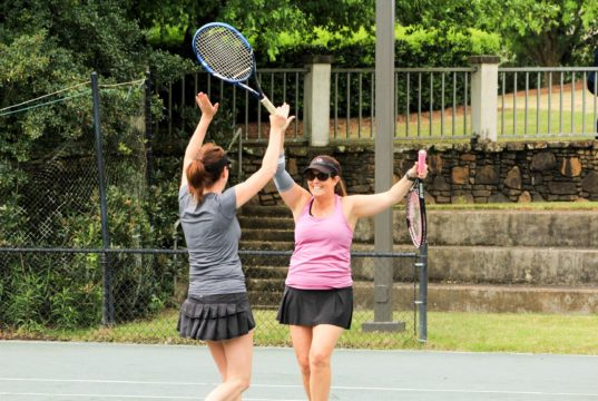 Two female tennis players celebrating a win