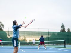 man serving in a tennis doubles match