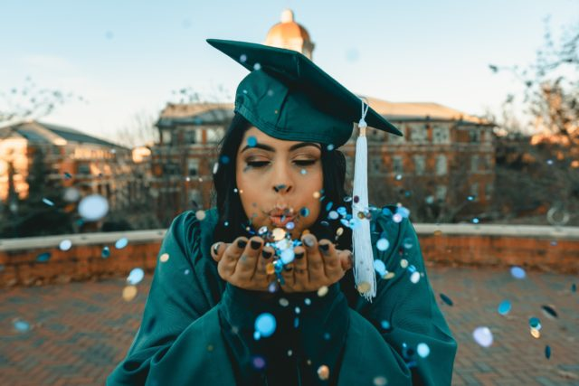 student in cap and gown blowing confetti
